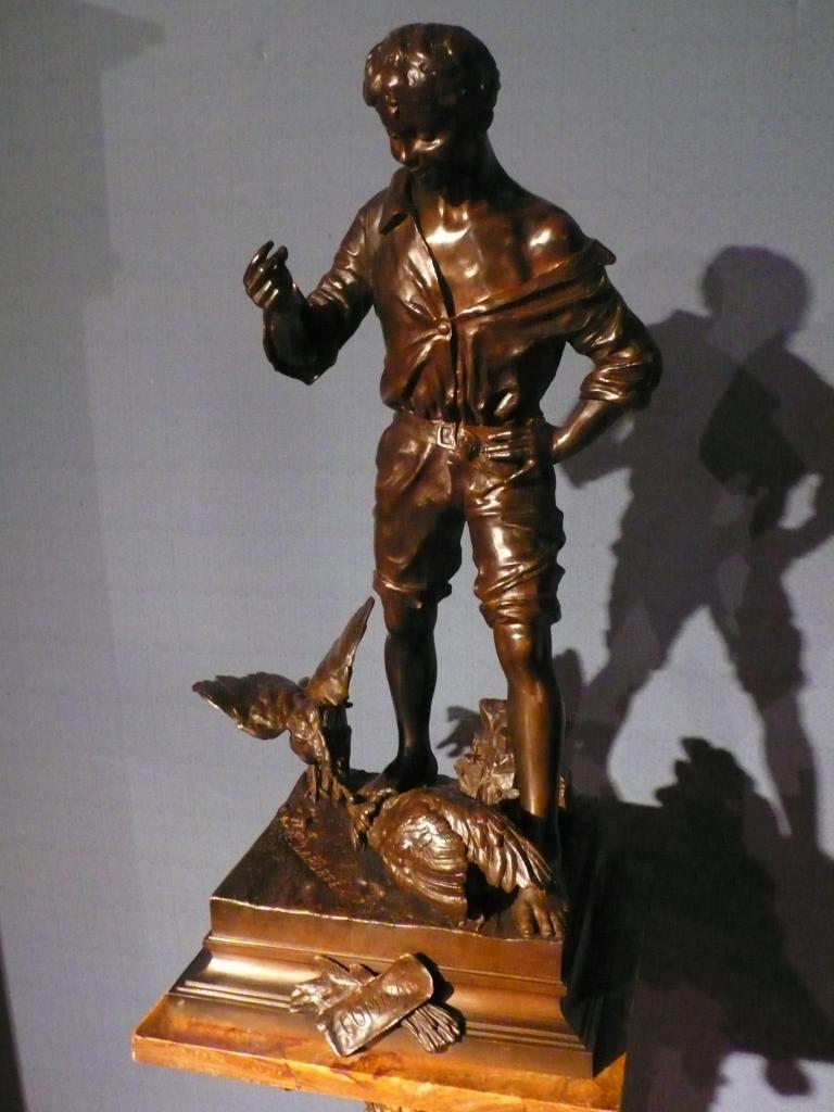 Bronze représentant un combat de coqs sous le regard d'un jeune garçon.